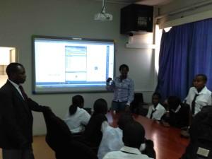Inviolata Sore demonstrates the SMART Board to visiting secondary school students